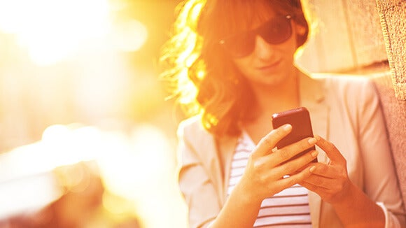 woman outside with sunglasses on in sunshine using mobile phone