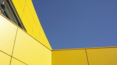 Yellow building against blue sky with information about salary survey